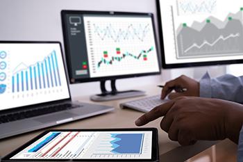 Dekstop, laptop en tablet met hierop verschillende grafieken die data weergeven