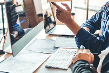 Overleg tussen 2 mensen die kijken naar code op een desktop