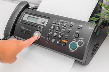 Een faxmachine waarop iemand op de verzendknop drukt