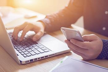 Iemand is zowel op een laptop als op een mobiele telefoon aan het werk