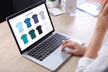 Een laptop met daarop een webshop pagina met t-shirts waar iemand naar kijkt