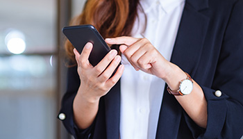 Een vrouw met een mobiele telefoon in haar hand, waar ze op aan het werk is