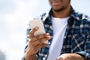 Een man die bezig is met zijn mobiele telefoon, waarbij hij een sms verstuurd