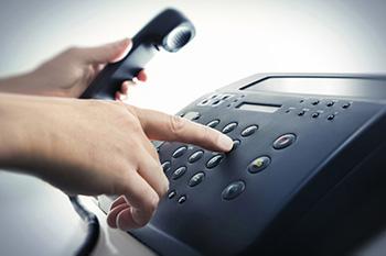 Iemand die via een vaste telefoon een servicenummer aan het intoetsen is
