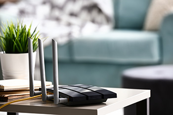 Een wifi router op een tafeltje met een plantje ernaast