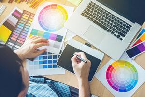 Een grafisch ontwerper met verschillende kleurenkaarten om zich heen en een teken tablet