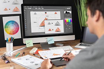 Een ontwerper bezig met een logo-ontwerp op de dekstop, met uitgeprinte versies om hem heen