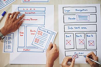 2 ontwerpers met papieren wireframes, bezig met het ontwerp van een website.